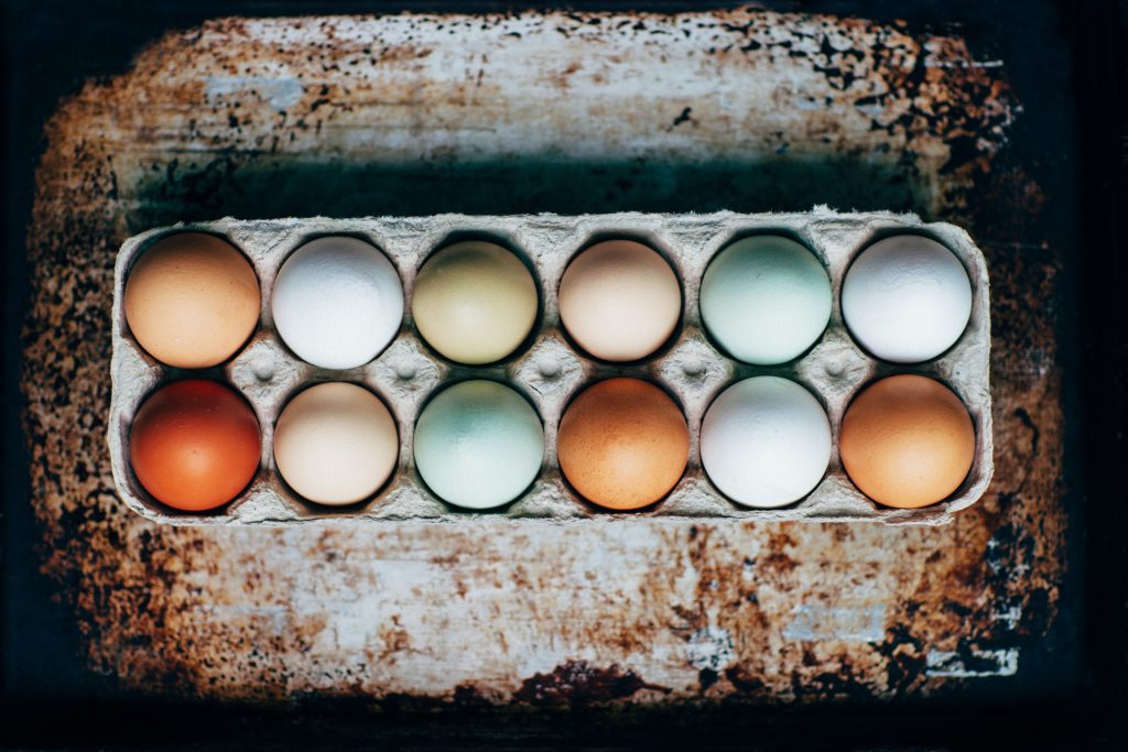 a photo of a carton of different colored eggs - a metaphor for belonging
