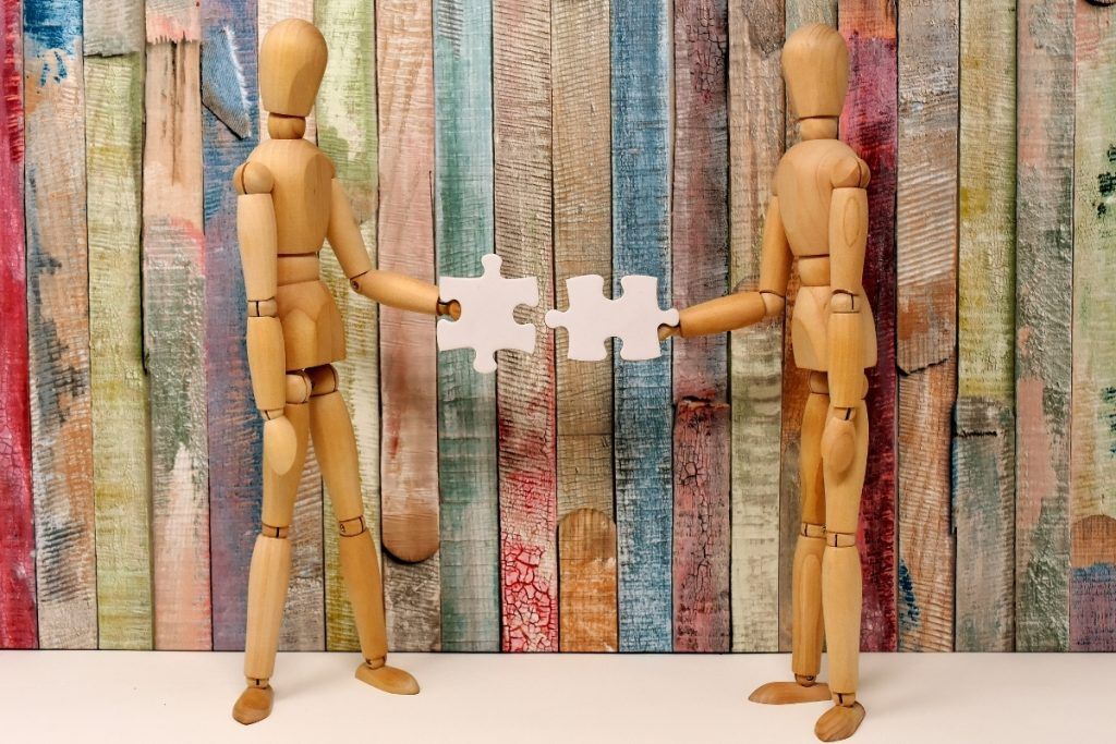 Two wooden dolls connecting puzzle pieces