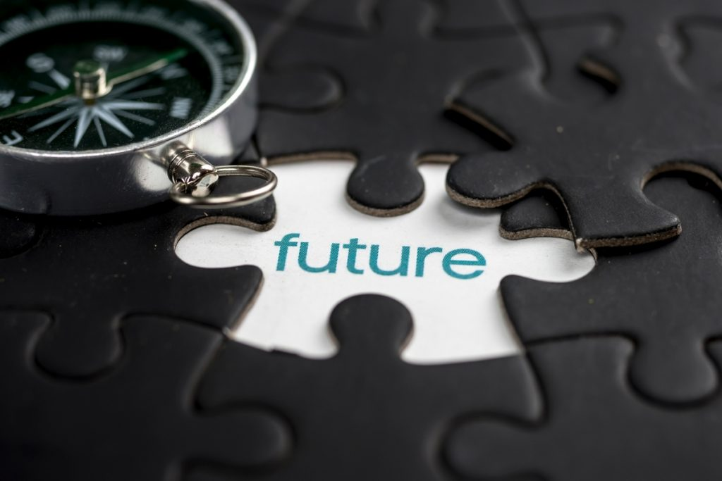 """A compass positioned over a puzzle with a missing piece that reads """"future"""""""